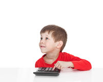 The five-year boy sitting at a white table and presses the button calculator Royalty Free Stock Images
