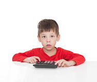 The five-year boy sitting at a white table and presses the button calculator Royalty Free Stock Image