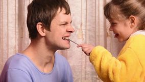 The five-year daughter playing doctor with Dad, Dad`s looked bad tooth stock video footage