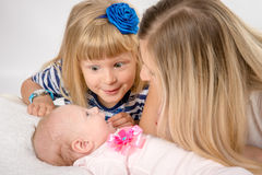 Five-year girl with amazement looks at his newborn sister Stock Images
