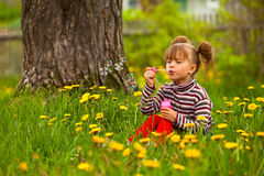 Five-year girl blowing soap bubbles in the park Stock Images