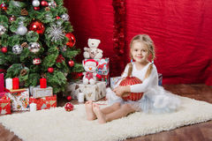 Five-year girl with Christmas ball in a tree Stock Image