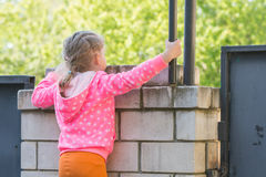 Five-year girl climbed on brick fence and looks for him Royalty Free Stock Images