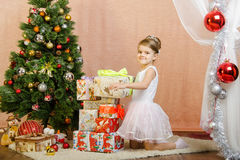 Five-year girl collects a tower of Christmas gifts Stock Image
