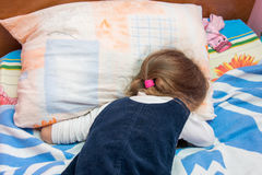 Five-year girl crying with his face buried in pillow stock photos
