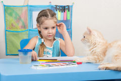 Five-year girl drawing pencils looked at the cat. Five-year girl draws pencils sitting at the table at home stock photography