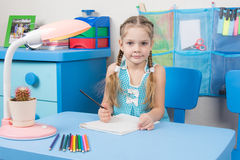 Five-year girl draws pencil in a notebook and looked into the frame Stock Photo
