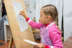 Five-year girl is engaged in drawing in the artists studio Stock Photo