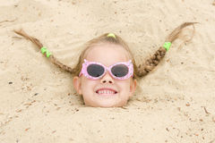 Five-year girl fell asleep on his head in the sand Royalty Free Stock Photo