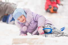 Five-year girl fell into the snow rolled down a hill and surrounded by other children. Five-year girl riding winter on a snowy hill surrounded by other children Royalty Free Stock Photos