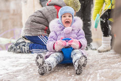 Five-year girl fun screaming slides down the icy hill. Five-year girl riding winter on a snowy hill surrounded by other children Royalty Free Stock Photo