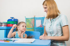 Five-year girl funny looks at the tutor who helps her to write letters correctly Royalty Free Stock Images