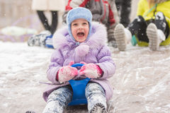 Five-year girl with a happy cry slipping ice slides. Five-year girl riding winter on a snowy hill surrounded by other children Royalty Free Stock Image