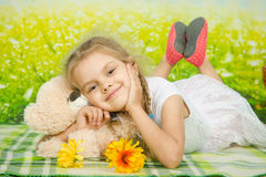 Five-year girl hugging a teddy bear lying on picnic rug Stock Photo