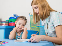 Five-year girl with interest looking notebook and listening to the explanation of the teacher Stock Images