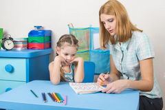 Five-year girl with interest looks at the teaching material explained by an adult Stock Images