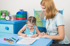 Five-year girl learns to write letters correctly, a tutor helps her Stock Photography