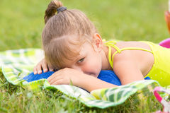 Five-year girl lies on a bed on green meadow and artfully looks aside royalty free stock photos