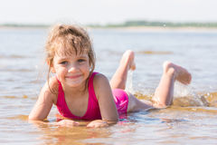 Five-year girl lies in water in shallows of the river and looking at the frame Stock Photo
