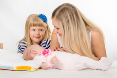 The five-year girl is looking at her mother who is looking at newborn daughter Stock Images