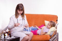Five-year girl looks frightened as doctor is preparing to make her a shot Royalty Free Stock Photography