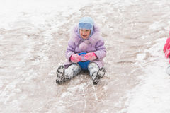 Five-year girl in the middle of the ice slides slides. Five-year girl riding winter on a snowy hill surrounded by other children Stock Photography