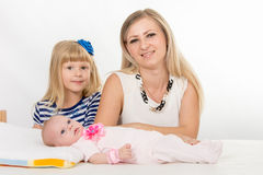 Five-year girl, mother and newborn baby are looking into the frame Stock Photos