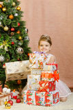 Five-year girl in a pile of Christmas gifts Stock Image