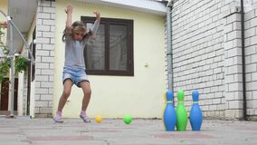 Five-year girl playing in a childrens bowling in yard stock video