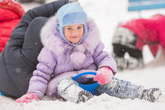 Five-year girl rolled down a hill sits. Five-year girl riding winter on a snowy hill surrounded by other children Royalty Free Stock Photos