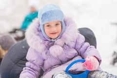 Five-year girl rolled down the hills with the other children. Five-year girl riding winter on a snowy hill surrounded by other children Royalty Free Stock Photos