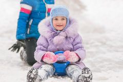 Five-year girl rolled down ice slides looked up. Five-year girl riding winter on a snowy hill surrounded by other children Royalty Free Stock Photography