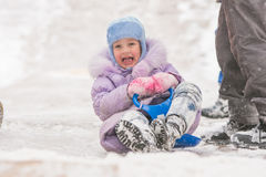 Five-year girl rolled down ice slides nearly crashed into other children. Five-year girl riding winter on a snowy hill surrounded by other children Stock Photography