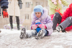 Five-year girl is rolling a frozen hill. Five-year girl riding winter on a snowy hill surrounded by other children Royalty Free Stock Image