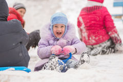 Five-year girl with rolling hills surrounded by other children. Five-year girl riding winter on a snowy hill surrounded by other children Stock Photography