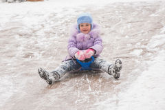 Five-year girl rolls on in the middle of the ice slides. Five-year girl riding winter on a snowy hill surrounded by other children Stock Photography