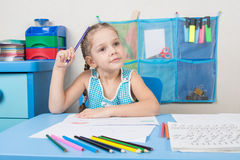 Five-year girl scratched his head and wondered pencil drawing picture at table Royalty Free Stock Images