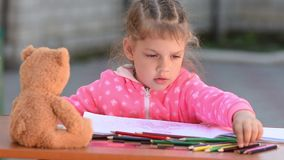 Five-year girl selects desired color pencil drawing in an album stock video footage