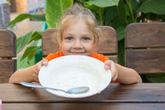 Five-year girl showing empty plate to eat Stock Images
