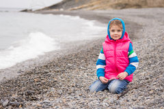 Five-year girl sits on a pebble beach in warm bright clothes on a cloudy day with a smile looks in the frame Stock Photography