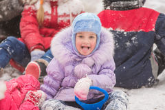 Five-year girl sitting in the snow surrounded by other children. Five-year girl riding winter on a snowy hill surrounded by other children Stock Image