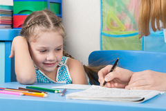 Five-year girl with a smile looking at my mother explaining how to write letters Stock Photo
