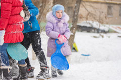 Five-year girl standing with hands ledyankah about icy hill. Five-year girl riding winter on a snowy hill surrounded by other children Stock Images