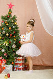 Five-year girl standing with toy snowman at Christmas tree Royalty Free Stock Photos
