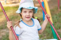 Five-year girl in summer panama rides on swing Stock Image