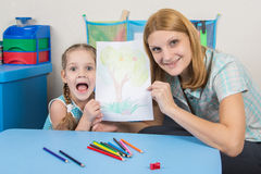 Five-year girl and the teacher happily show drawn on a sheet of wood Stock Photography
