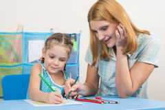 Five-year girl and young mother together paint a picture with crayons Stock Image