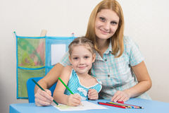 Five-year girl and young mother together paint a picture on a sheet of paper Royalty Free Stock Image