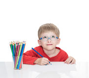 The five-year-old boy in blue points sits at a white table and and draws pencils. Isolated on a white background Royalty Free Stock Photo