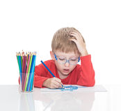 The five-year-old boy in blue points sits at a white table and and draws pencils Stock Photos